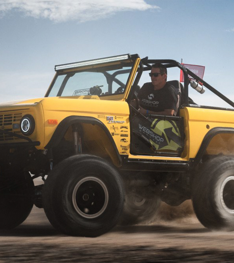 The owner driving his yellow bronco in the desert.